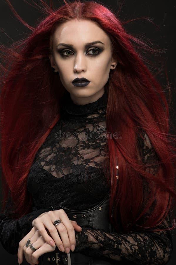 Νέα γυναίκα με την κόκκινη τρίχα στο μαύρο γοτθικό κοστούμι στοκ φωτογραφία με δικαίωμα ελεύθερης χρήσης