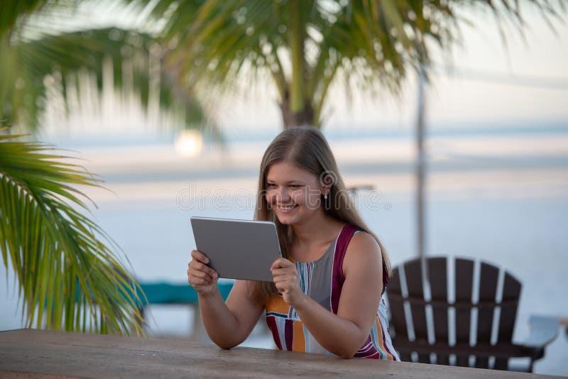 Νέα γυναίκα με την ταμπλέτα στην παραλία στοκ φωτογραφία με δικαίωμα ελεύθερης χρήσης