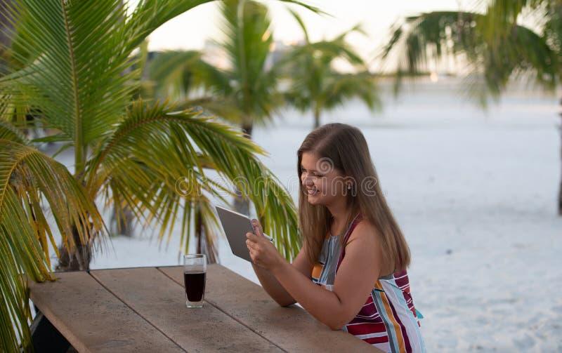 Νέα γυναίκα με την ταμπλέτα στην παραλία στοκ φωτογραφίες με δικαίωμα ελεύθερης χρήσης