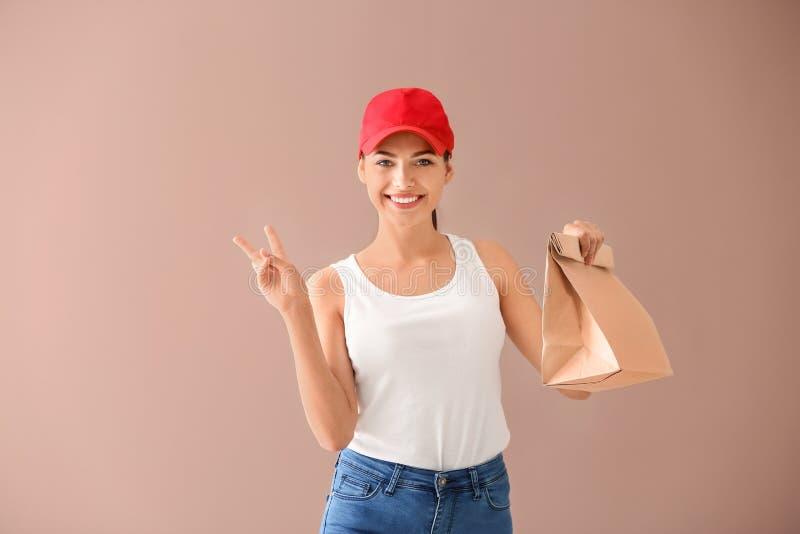 Νέα γυναίκα με την τσάντα εγγράφου που παρουσιάζει σημάδι νίκης στο υπόβαθρο χρώματος Υπηρεσία παράδοσης τροφίμων στοκ φωτογραφίες με δικαίωμα ελεύθερης χρήσης