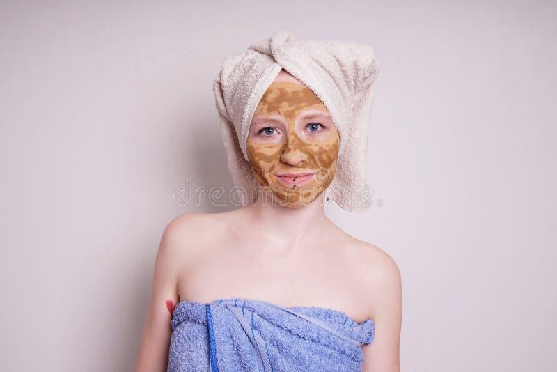 Νέα γυναίκα με της του προσώπου μάσκας ομορφιάς γης ή αργίλου που τυλίγεται τη θεραπεία στην πετσέτα στοκ φωτογραφίες