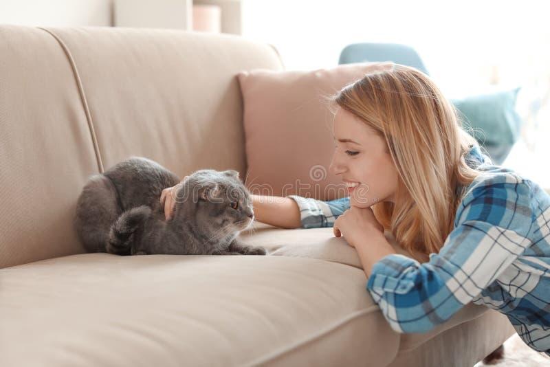 Νέα γυναίκα με τη γάτα κατοικίδιων ζώων της στο σπίτι στοκ φωτογραφία με δικαίωμα ελεύθερης χρήσης