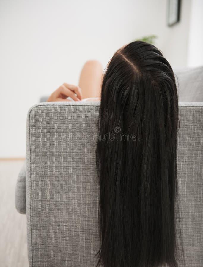 Νέα γυναίκα με τη μακριά μαύρη τρίχα που βάζει στο ντιβάνι στοκ φωτογραφίες με δικαίωμα ελεύθερης χρήσης