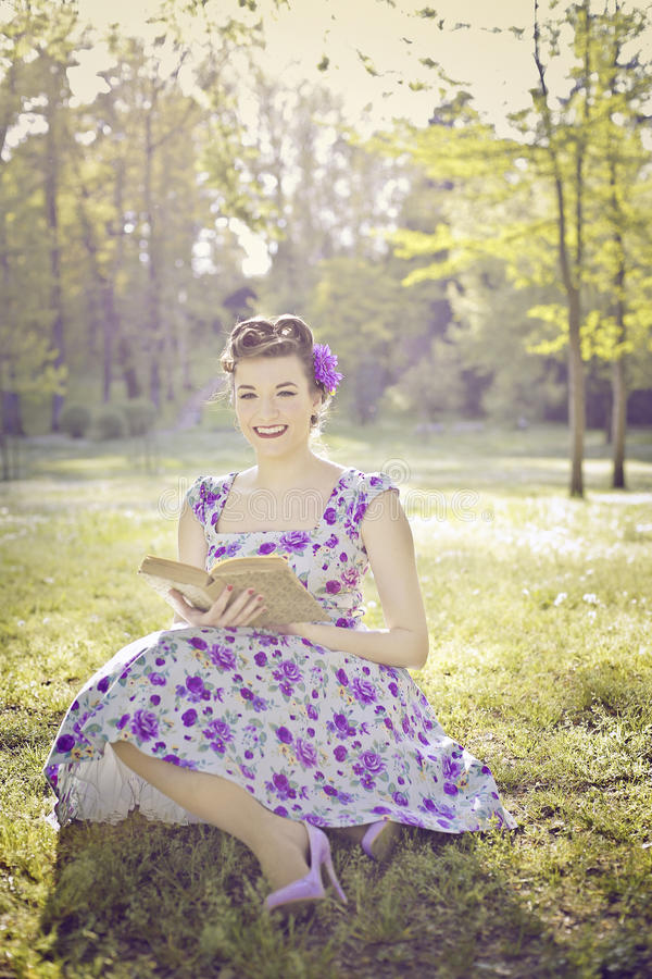 Νέα γυναίκα με τη μακρυμάλλη συνεδρίαση στην ανάγνωση καθισμάτων παραθύρων στοκ εικόνα με δικαίωμα ελεύθερης χρήσης
