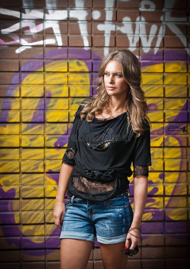Νέα γυναίκα με τη μαύρη μπλούζα και μακρυμάλλης ενάντια σε έναν τοίχο γκράφιτι στοκ εικόνα