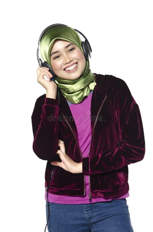 Νέα γυναίκα με τη μουσική ακούσματος ακουστικών στο άσπρο υπόβαθρο στοκ φωτογραφίες