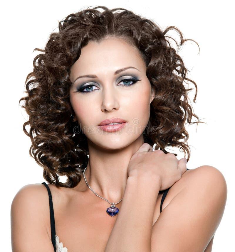 Νέα γυναίκα με τη μόδα makeup και το σγουρό hai στοκ εικόνες
