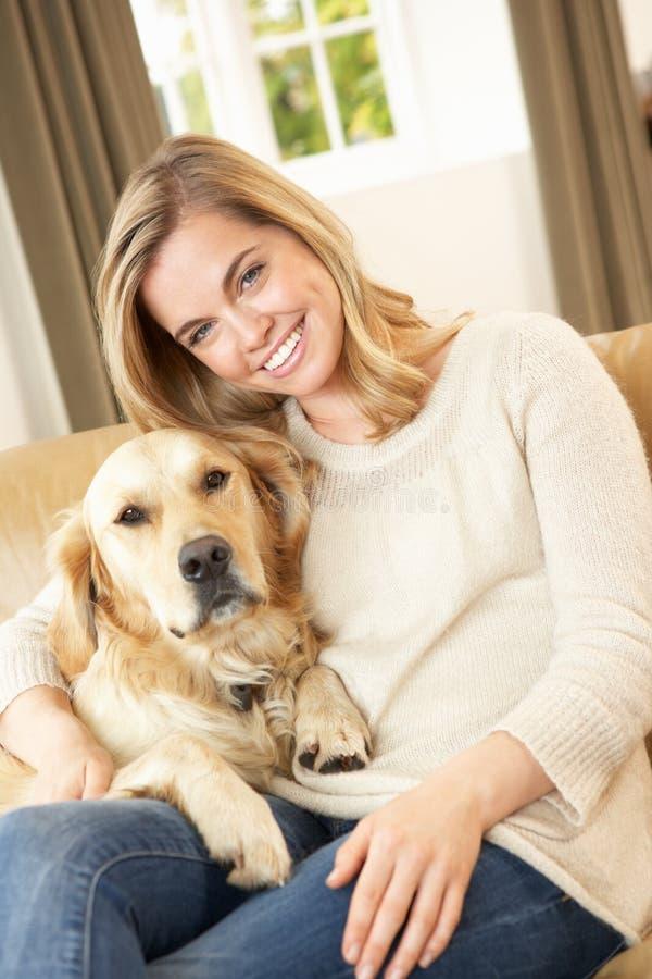 Νέα γυναίκα με τη συνεδρίαση σκυλιών στον καναπέ στοκ εικόνες