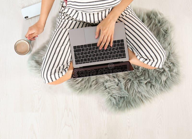 Νέα γυναίκα με τη συνεδρίαση lap-top στο πάτωμα, τοπ άποψη στοκ εικόνες