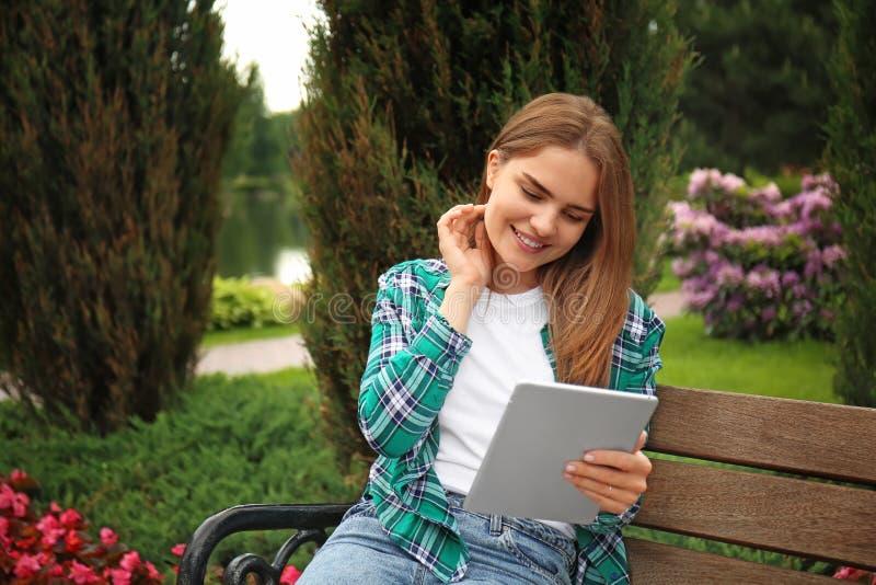 Νέα γυναίκα με τη συνεδρίαση PC ταμπλετών στον ξύλινο πάγκο στο πάρκο στοκ φωτογραφία με δικαίωμα ελεύθερης χρήσης