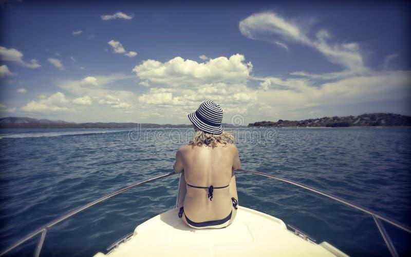 Νέα γυναίκα με τη συνεδρίαση καπέλων στο μέτωπο μιας βάρκας πανιών στοκ εικόνα με δικαίωμα ελεύθερης χρήσης