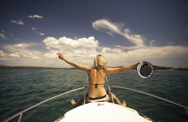 Νέα γυναίκα με τη συνεδρίαση καπέλων στο μέτωπο μιας βάρκας πανιών στοκ φωτογραφία με δικαίωμα ελεύθερης χρήσης