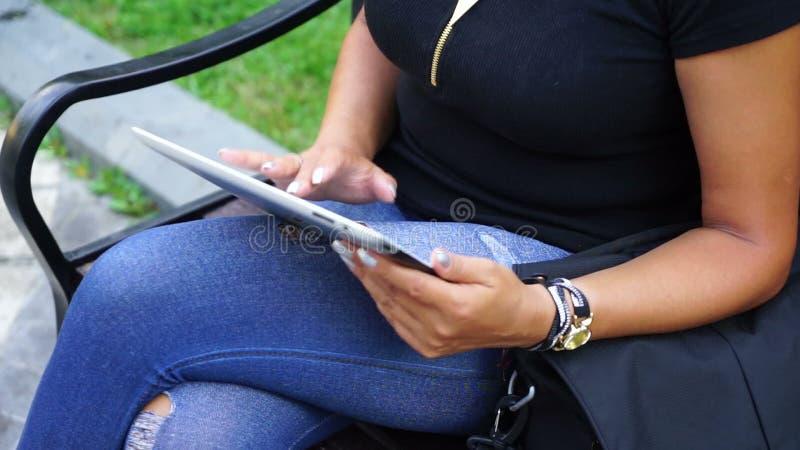 Νέα γυναίκα με τη συνεδρίαση υπολογιστών ταμπλετών στο πάρκο πόλεων φιλμ μικρού μήκους