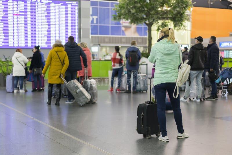 Νέα γυναίκα με τη χειραποσκευή στο διεθνές τερματικό αερολιμένων, που εξετάζει τον πίνακα πληροφοριών, που ελέγχει την πτήση της  στοκ φωτογραφίες με δικαίωμα ελεύθερης χρήσης
