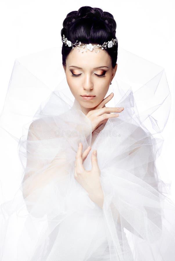 Νέα γυναίκα με τις ιδιαίτερες προσοχές που απομονώνεται στο άσπρο υπόβαθρο στούντιο που ντύνεται στο ακρωτήριο του organza και τη στοκ φωτογραφία