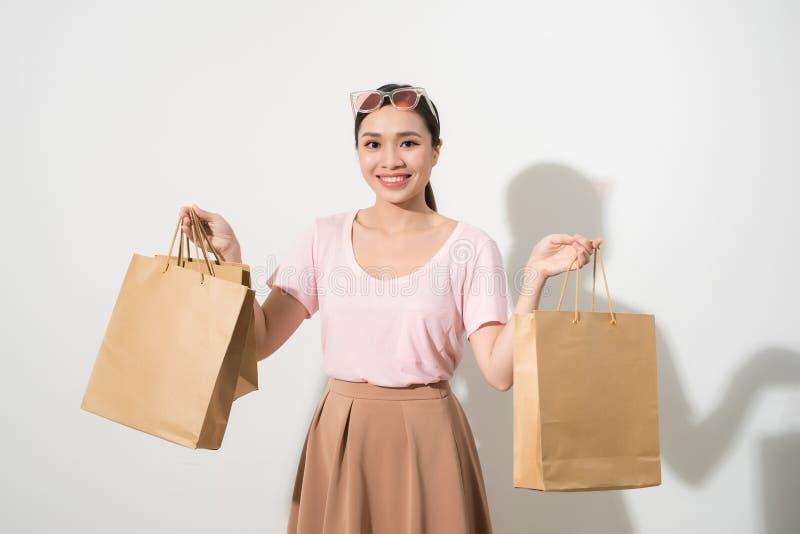 Νέα γυναίκα με τις τσάντες αγορών πέρα από το άσπρο υπόβαθρο στοκ φωτογραφία με δικαίωμα ελεύθερης χρήσης