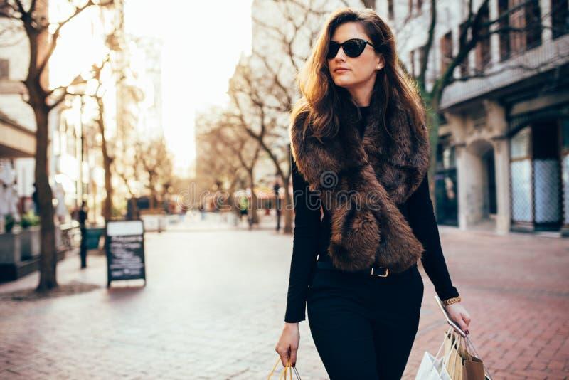 Νέα γυναίκα με τις τσάντες αγορών που περπατά στην οδό στοκ εικόνες