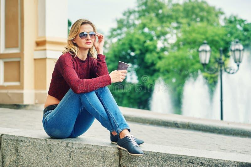 Νέα γυναίκα με τον καφέ στις οδούς στοκ φωτογραφία με δικαίωμα ελεύθερης χρήσης