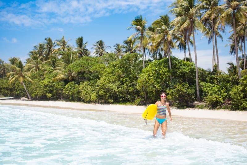 Νέα γυναίκα με τον πίνακα κυματωγών στην τροπική παραλία στοκ εικόνα με δικαίωμα ελεύθερης χρήσης