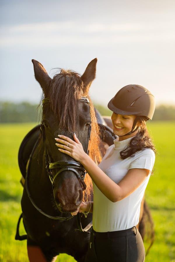 Νέα γυναίκα με το άλογό της στην ανατολή στοκ εικόνες με δικαίωμα ελεύθερης χρήσης