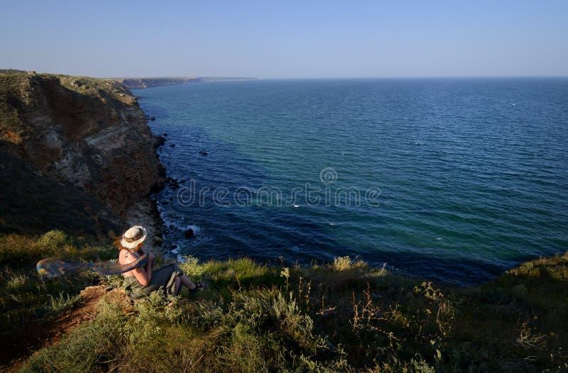 Νέα γυναίκα με το καπέλο που κοιτάζει πέρα από τη θάλασσα από έναν υψηλό απότομο βράχο στοκ φωτογραφίες
