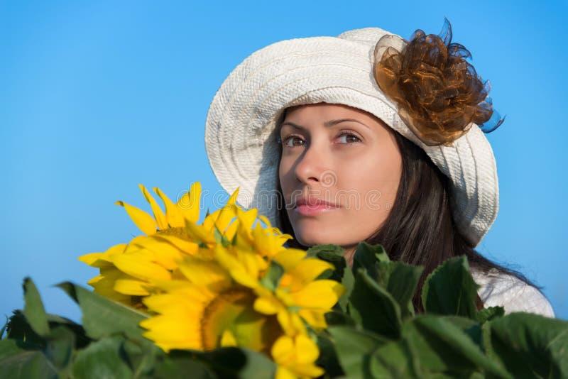 Νέα γυναίκα με το καπέλο και τους ηλίανθους στοκ εικόνα