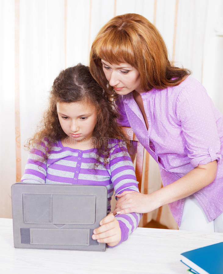 Νέα γυναίκα με το κορίτσι που χρησιμοποιεί τον υπολογιστή ταμπλετών στοκ φωτογραφία με δικαίωμα ελεύθερης χρήσης