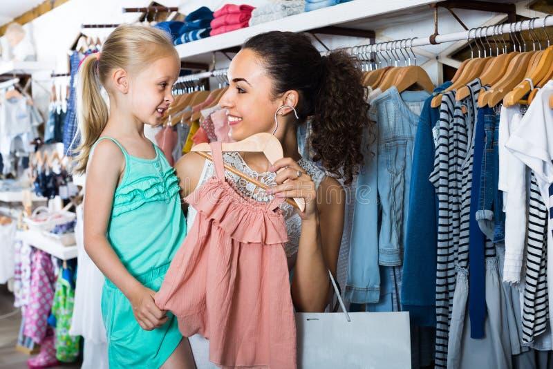 Νέα γυναίκα με το μικρό κορίτσι που επιλέγει το ρόδινο φόρεμα στην ενδυμασία παιδιών στοκ φωτογραφίες
