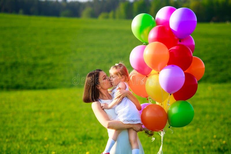 Νέα γυναίκα με το παιδί στο άσπρο φόρεμα με το ζωηρόχρωμο outdo μπαλονιών στοκ εικόνες