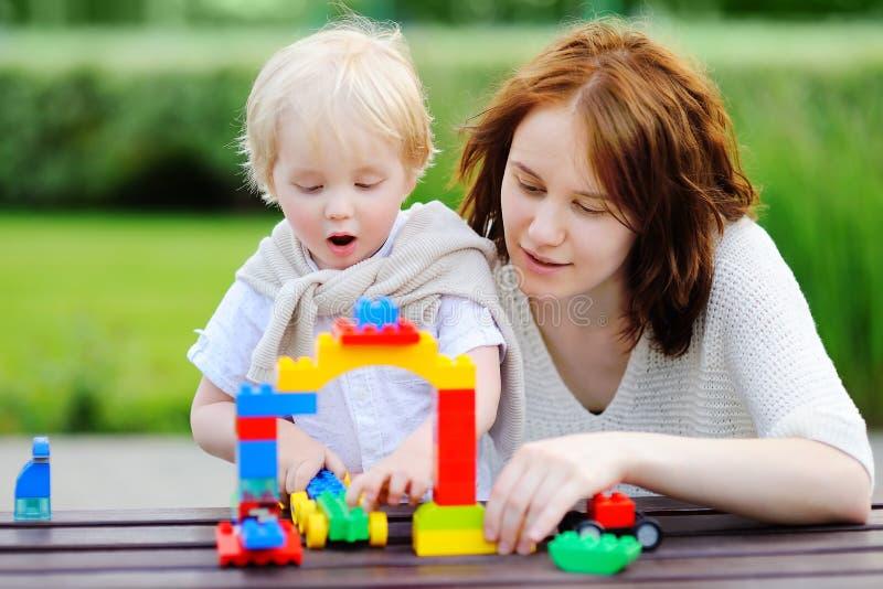 Νέα γυναίκα με το παιχνίδι γιων μικρών παιδιών με τους πλαστικούς φραγμούς στοκ εικόνες