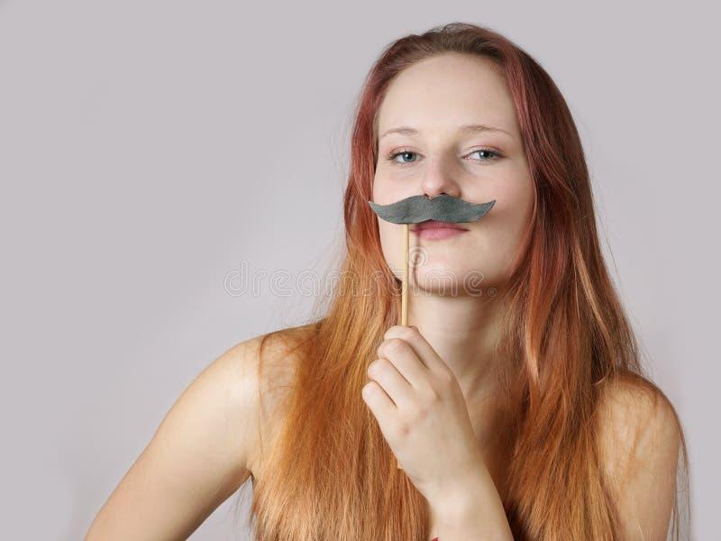 Νέα γυναίκα με το πλαστό moustache στοκ εικόνα