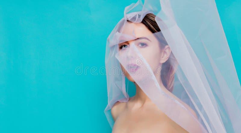 Νέα γυναίκα με το ρόδινο Tulle στο μπλε υπόβαθρο στοκ εικόνες με δικαίωμα ελεύθερης χρήσης