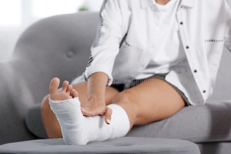 Νέα γυναίκα με το σπασμένο πόδι στη χυτή συνεδρίαση στον καναπέ στοκ φωτογραφία με δικαίωμα ελεύθερης χρήσης