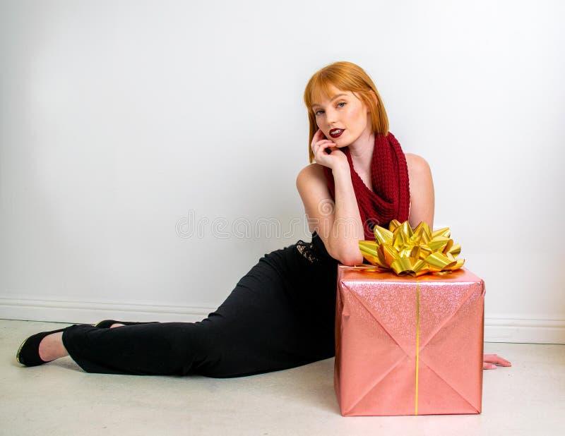 Νέα γυναίκα με το τυλιγμένο δώρο Χριστουγέννων στοκ φωτογραφία
