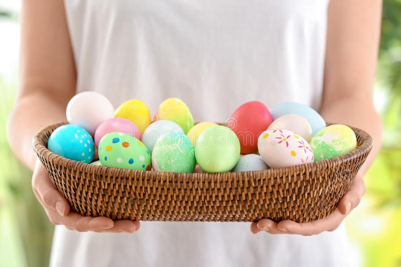 Νέα γυναίκα με το ψάθινο σύνολο κύπελλων των ζωηρόχρωμων αυγών Πάσχας, κινηματογράφηση σε πρώτο πλάνο στοκ εικόνες με δικαίωμα ελεύθερης χρήσης