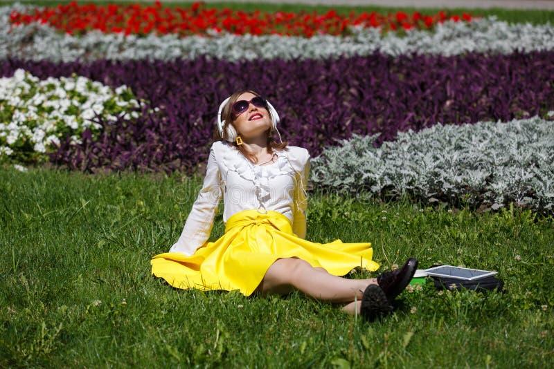 Νέα γυναίκα με το PC ταμπλετών στο πάρκο στοκ φωτογραφίες