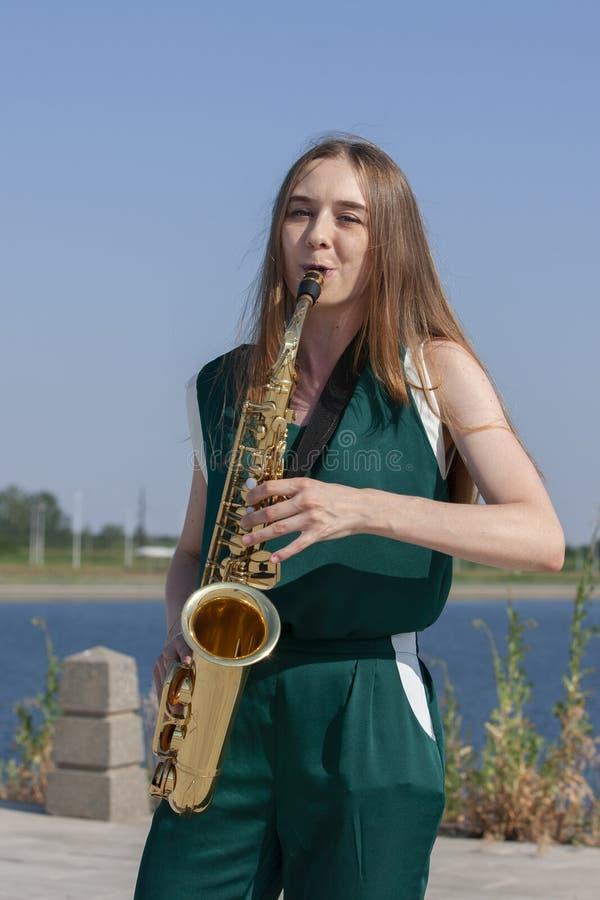Νέα γυναίκα με το saxophone στο πάρκο στοκ εικόνα