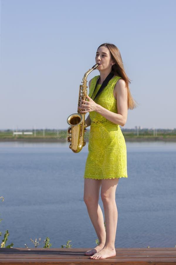 Νέα γυναίκα με το saxophone στο πάρκο στοκ φωτογραφία