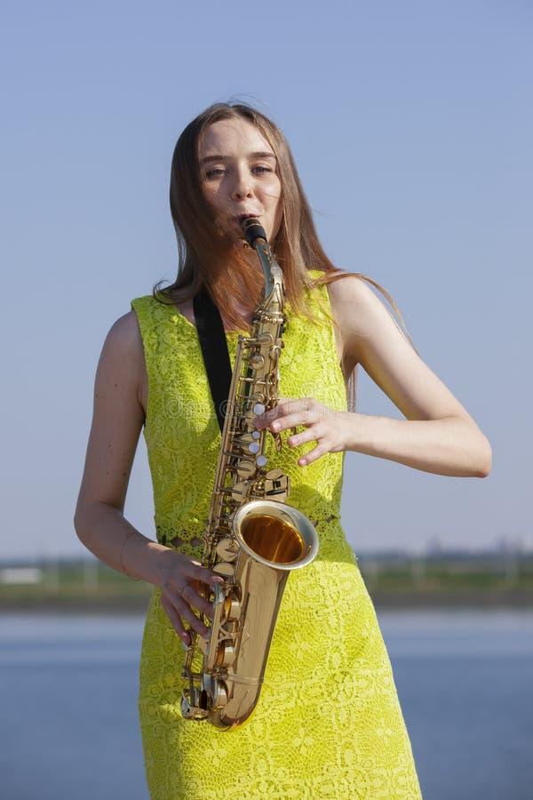 Νέα γυναίκα με το saxophone στο πάρκο στοκ εικόνες