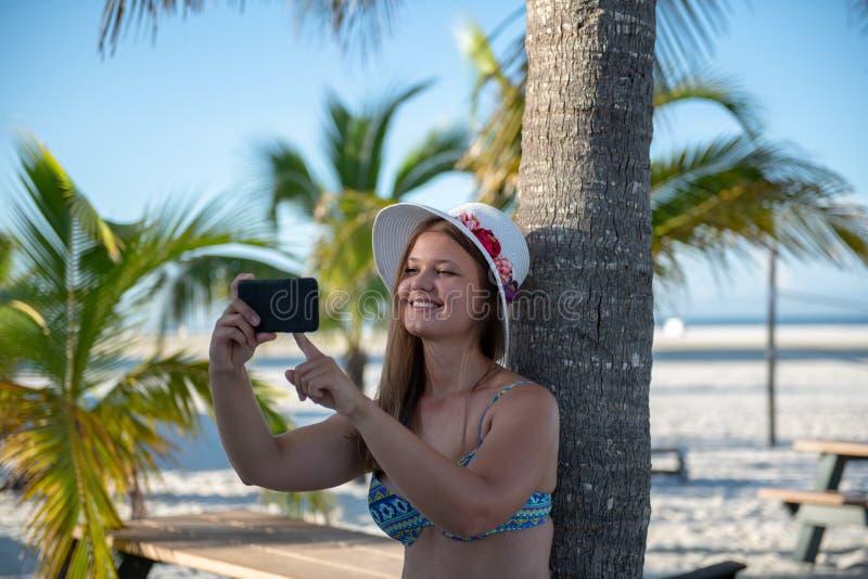 Νέα γυναίκα με το smartphone μπροστά από το φοίνικα στοκ φωτογραφίες με δικαίωμα ελεύθερης χρήσης