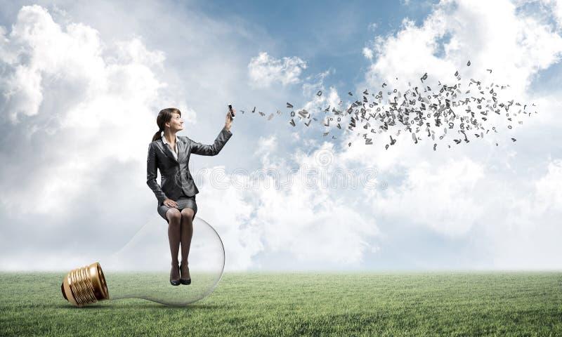 Νέα γυναίκα με το smartphone που στέλνει το μήνυμα κειμένου στοκ εικόνες