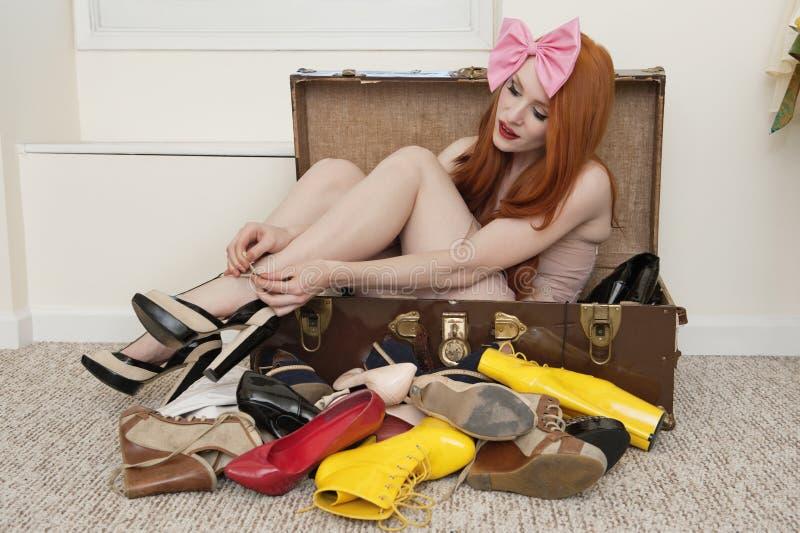 Νέα γυναίκα με headband τόξων τα δένοντας υποδήματα καθμένος στη βαλίτσα στοκ εικόνα