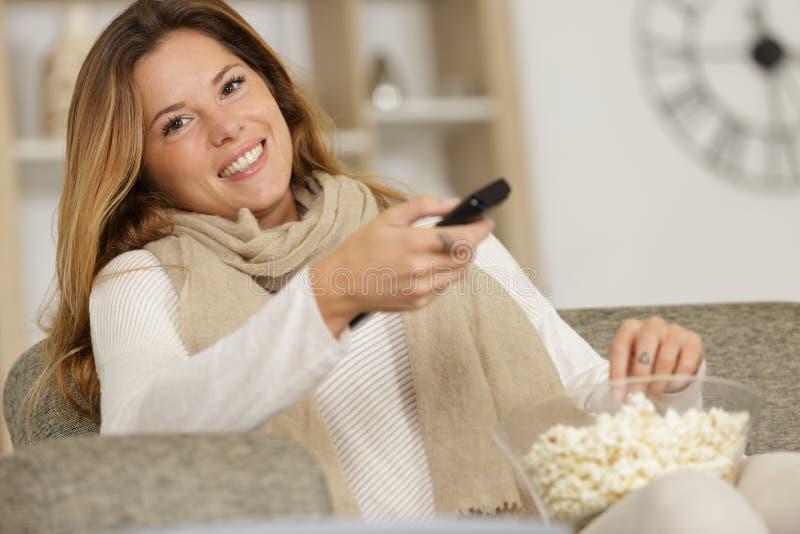 Νέα γυναίκα με popcorn την εκμετάλλευση κύπελλων μακρινή στοκ φωτογραφίες