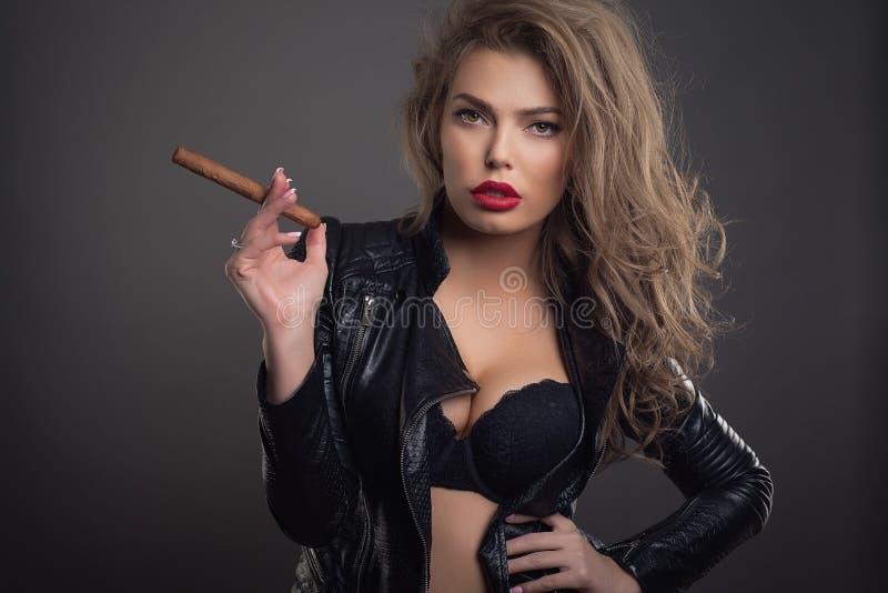 Νέα γυναίκα με sigar στο σκοτεινό πυροβολισμό στούντιο υποβάθρου στοκ φωτογραφία