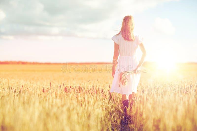 Νέα γυναίκα με spikelets δημητριακών που περπατά στον τομέα στοκ εικόνες με δικαίωμα ελεύθερης χρήσης