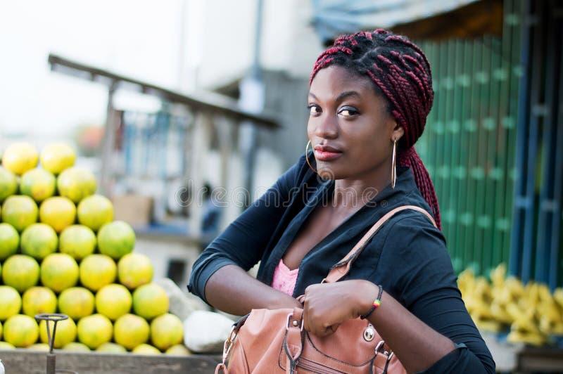 Νέα γυναίκα μπροστά από έναν σωρό των πορτοκαλιών, που κοιτάζει στην τσάντα στοκ εικόνες με δικαίωμα ελεύθερης χρήσης