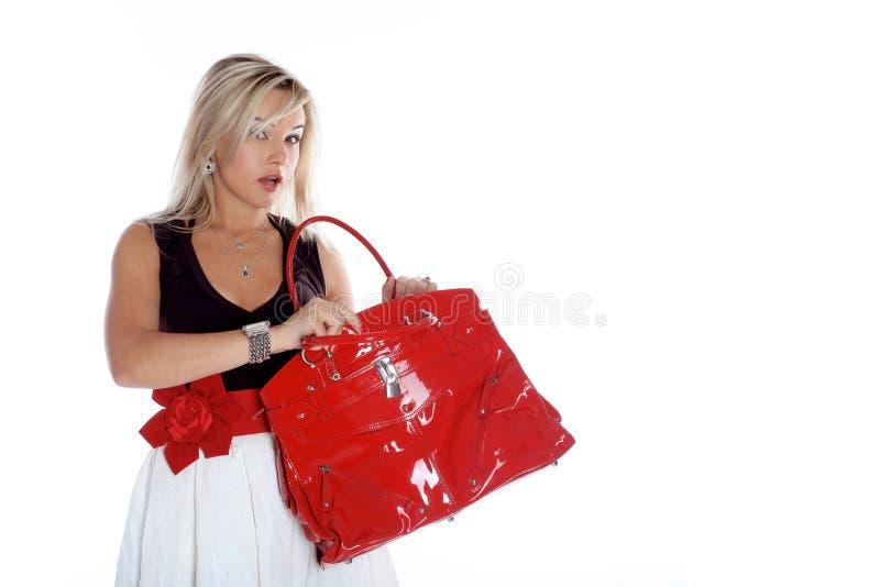 Νέα γυναίκα μόδας με την κόκκινη τσάντα στοκ φωτογραφίες