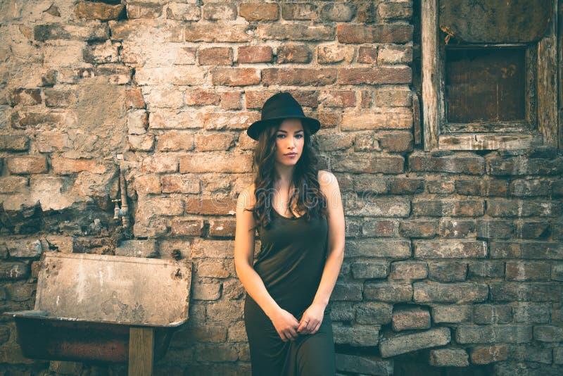 Νέα γυναίκα μόδας με τη στάση καπέλων στο μπροστινό παλαιό εγκαταλειμμένο σπίτι στοκ εικόνες με δικαίωμα ελεύθερης χρήσης