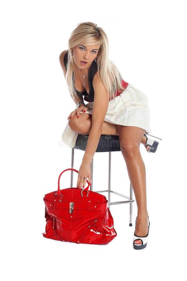 Νέα γυναίκα μόδας που παίρνει την κόκκινη τσάντα στοκ φωτογραφία