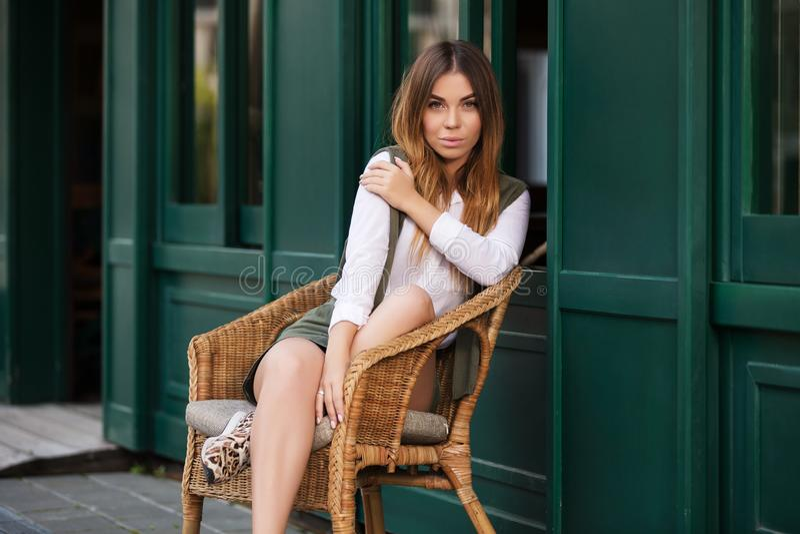 Νέα γυναίκα μόδας στην άσπρη συνεδρίαση μπλουζών στην ψάθινη καρέκλα στοκ φωτογραφίες